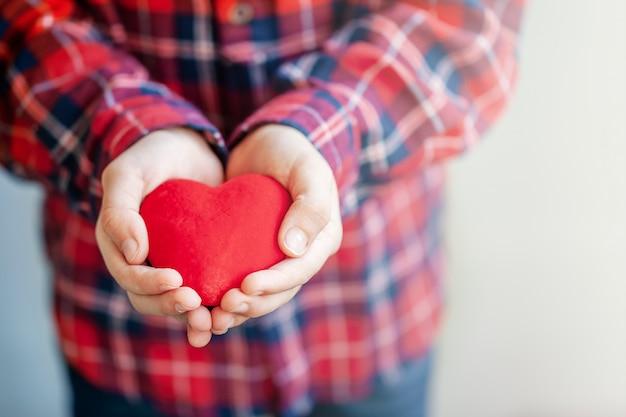 Jonge geitjeshanden die rood hart en liefde in de dag van de valentijnskaart geven.