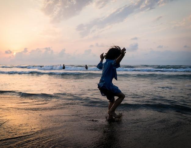 Jonge geitjesilhouetten die gelukkige tijd op overzees strand hebben dichtbij zonsondergang
