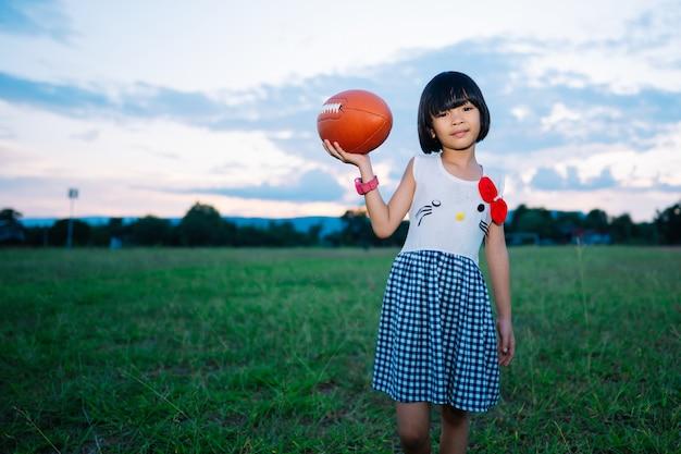 Jonge geitjesmeisje die amerikaanse voetbal bij de zonsondergangzomer spelen