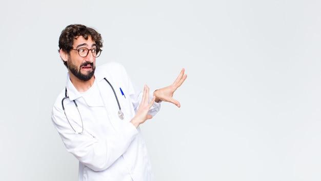 Jonge gekke bebaarde arts man over kopie ruimte muur