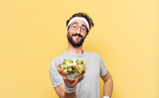 Jonge gekke bebaarde atleet gelukkige uitdrukking en met een salade
