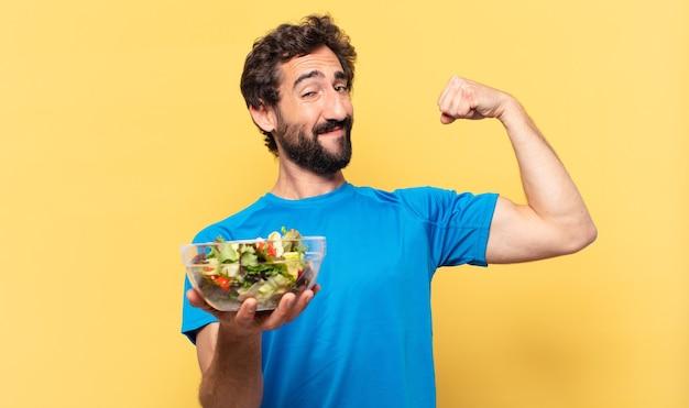 Jonge gekke bebaarde atleet gelukkige uitdrukking, salade vasthouden en biceps laten zien showing