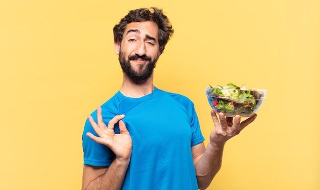Jonge gekke bebaarde atleet met een gelukkige uitdrukking die salade vasthoudt