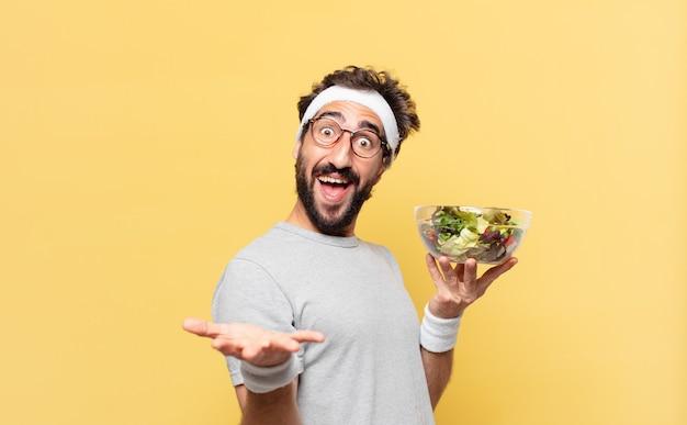 Jonge gekke bebaarde atleet verraste uitdrukking en houdt een salade vast