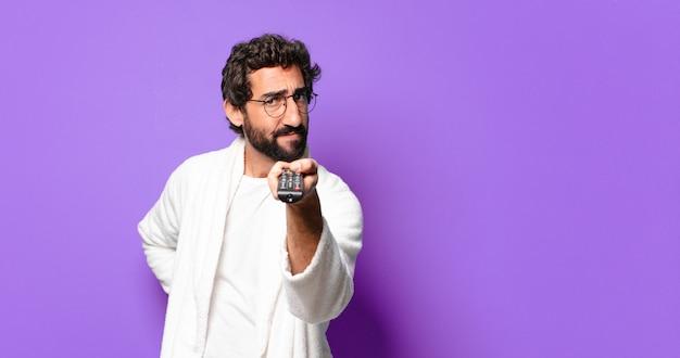 Jonge gekke bebaarde man badjas dragen met een afstandsbediening van de televisie