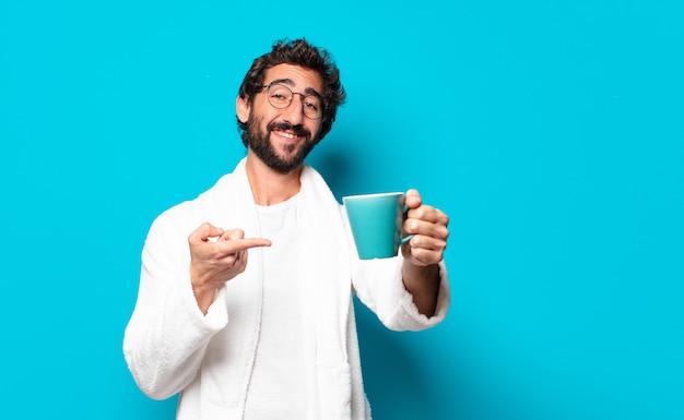 Jonge gekke bebaarde man badjas met een koffiekopje dragen