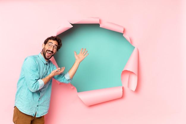 Jonge gekke bebaarde man blij en verrast uitdrukking papier gat lege achtergrond concept