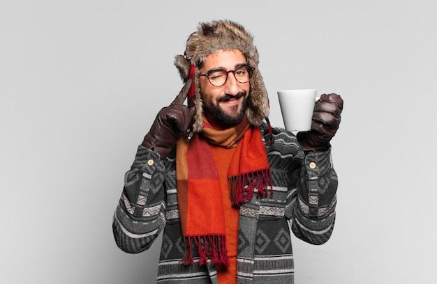 Jonge gekke bebaarde man denken en winterkleren dragen