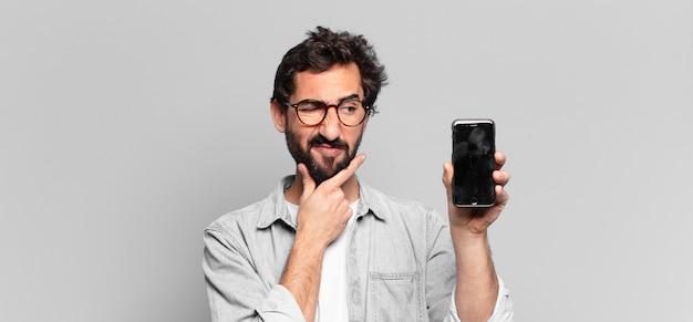 Jonge gekke bebaarde man. denken of twijfelen expressie. telefoon scherm concept