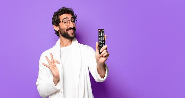 Jonge gekke bebaarde man die een badjas draagt met een afstandsbediening van een televisie