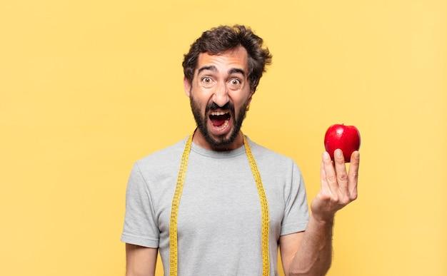 Jonge gekke bebaarde man die een boze uitdrukking op dieet is en een appel vasthoudt