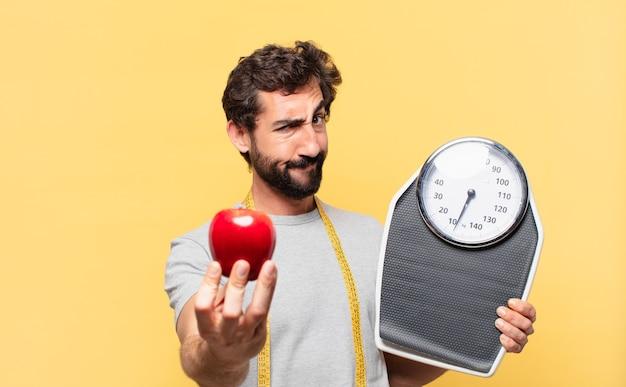 Jonge gekke bebaarde man die een boze uitdrukking op dieet is en een weegschaal en een appel vasthoudt
