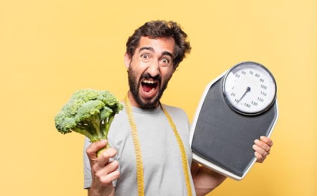 Jonge gekke bebaarde man die een boze uitdrukking op dieet is en een weegschaal vasthoudt