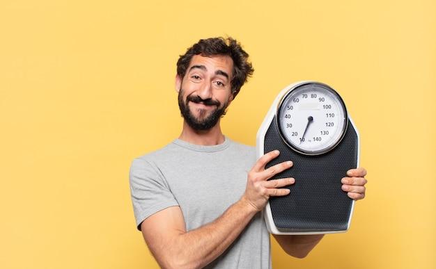 Jonge gekke bebaarde man die een gelukkige uitdrukking op dieet heeft en een weegschaal vasthoudt