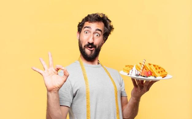 Jonge gekke bebaarde man die een gelukkige uitdrukking op dieet heeft en wafels vasthoudt