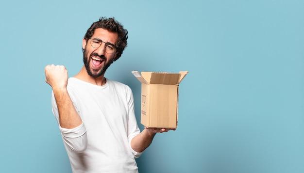 Jonge gekke bebaarde man die een kartonnen pakket reciteert