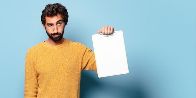 Jonge gekke bebaarde man die een vel papier laat zien
