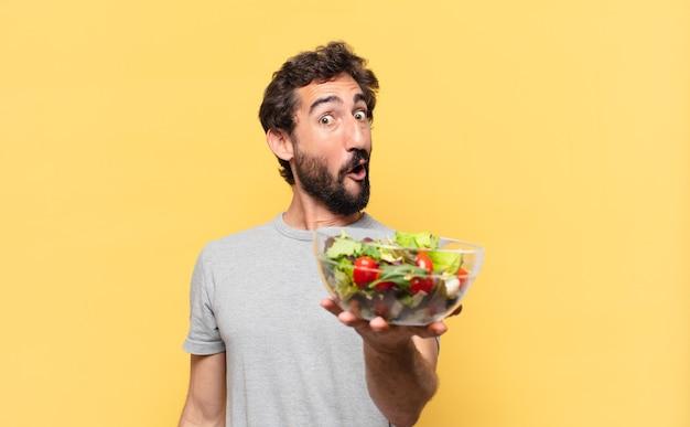 Jonge gekke bebaarde man die een verbaasde uitdrukking volgt en een salade vasthoudt holding