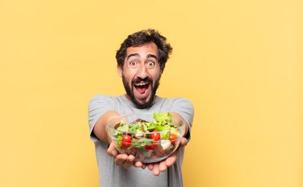 Jonge gekke bebaarde man die een verbaasde uitdrukking volgt en een salade vasthoudt