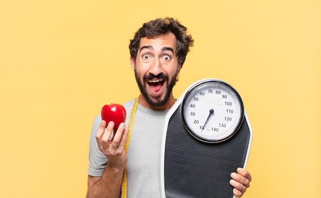 Jonge gekke bebaarde man die een verbaasde uitdrukking volgt en een weegschaal en een appel vasthoudt holding