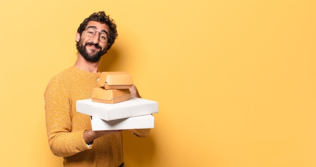 Jonge gekke bebaarde man die fastfood heeft weggehaald met een kopieerruimte