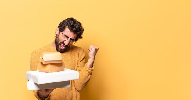 Jonge gekke bebaarde man die fastfood met een kopie ruimte heeft weggehaald