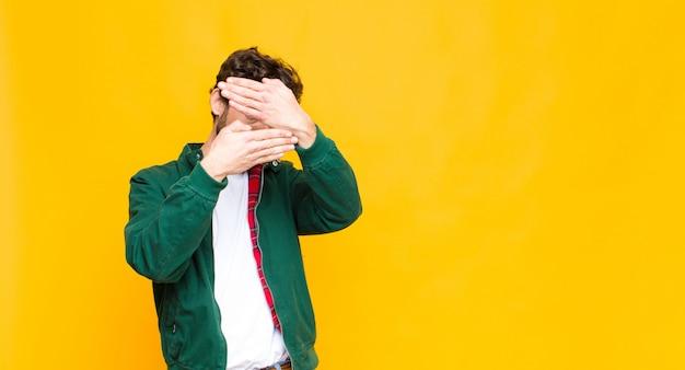 Jonge gekke bebaarde man die gezicht bedekt met beide handen nee zegt! afbeeldingen weigeren of foto's verbieden tegen een vlakke muur