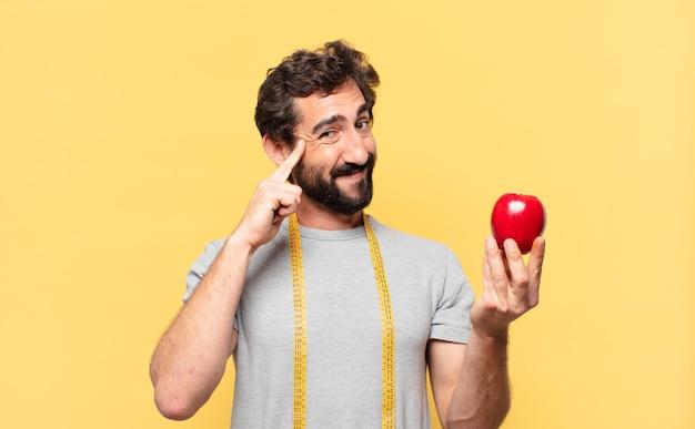 Jonge gekke bebaarde man die op dieet is, denkt aan een uitdrukking en houdt een appel vast