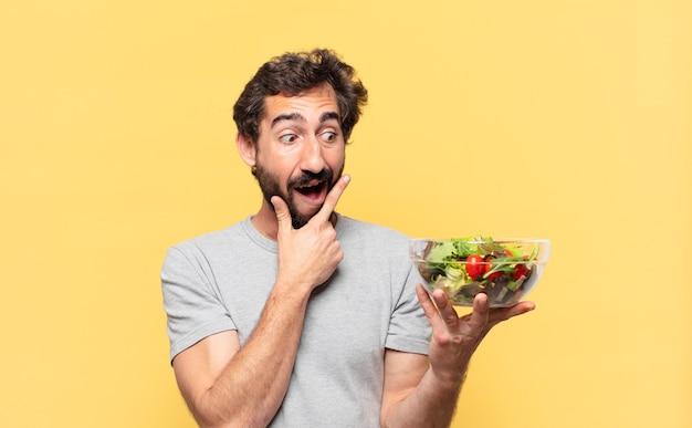 Jonge, gekke, bebaarde man die op dieet is, denkt aan een uitdrukking en houdt een salade vast