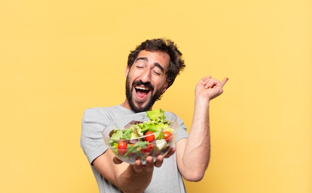 Jonge gekke bebaarde man die op dieet is en een overwinning viert en een salade vasthoudt