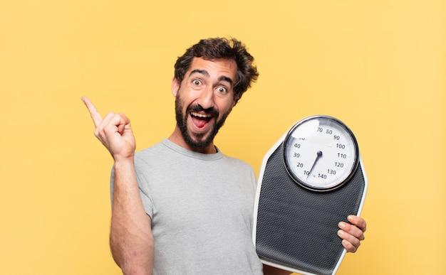 Jonge gekke bebaarde man die op dieet is en een overwinning viert en een weegschaal vasthoudt