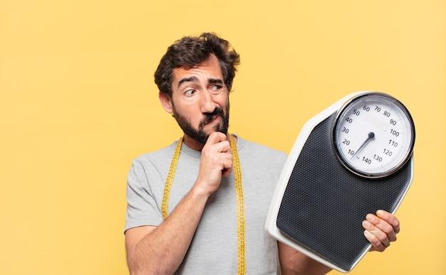 Jonge, gekke, bebaarde man die op dieet is, twijfelt of een onzekere uitdrukking heeft en een weegschaal vasthoudt