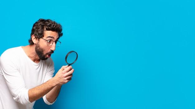 Jonge gekke bebaarde man die op zoek is en probeert te vinden met een vergrootglas