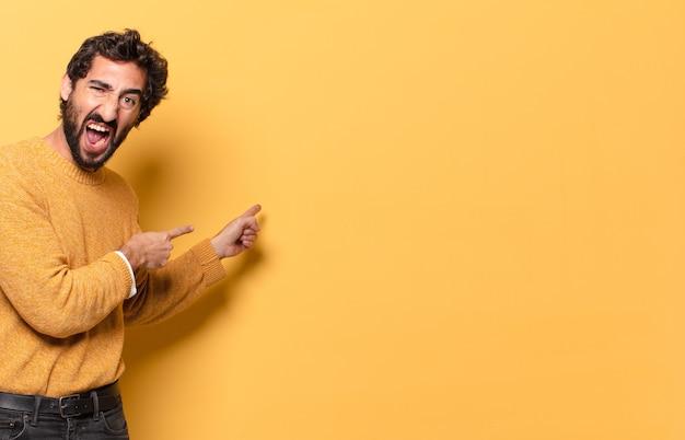 Jonge gekke bebaarde man die uitdrukt met een kopieerruimte