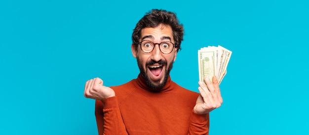 Jonge gekke bebaarde man. een triomf vieren als een winnaar. dollar biljetten concept
