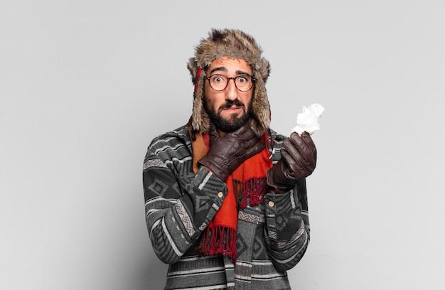 Jonge gekke bebaarde man en het dragen van winterkleren. ziekte concept