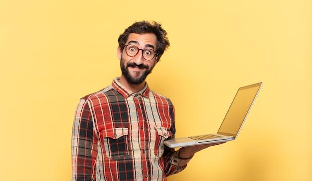 Jonge gekke bebaarde man gelukkige uitdrukking en een laptop