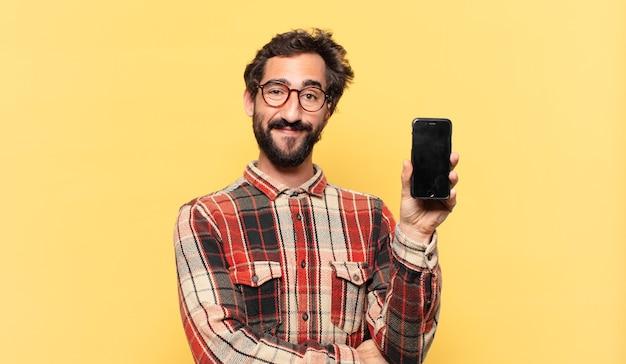 Jonge gekke bebaarde man gelukkige uitdrukking en met een telefoon