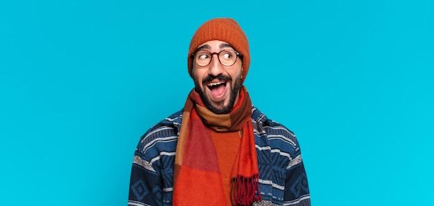 Jonge gekke bebaarde man geschokt of verrast uitdrukking en winterkleren dragen wearing