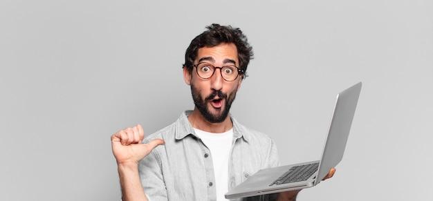 Jonge gekke bebaarde man. geschokte of verbaasde uitdrukking. laptop concept