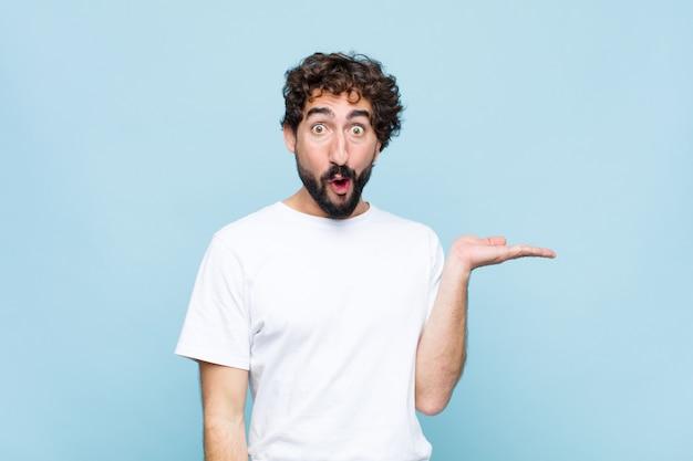 Jonge gekke bebaarde man kijkt verbaasd en geschokt, met zijn mond open van een voorwerp met een open hand aan de zijkant over de muur