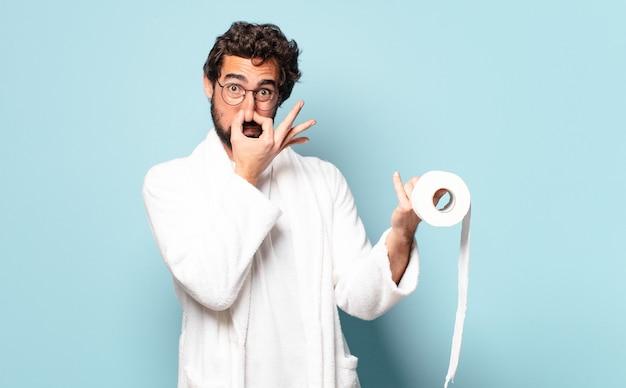 Jonge gekke bebaarde man met badjas en toiletpapier