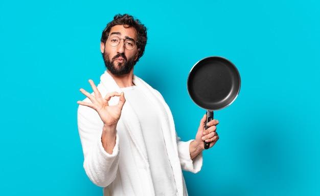Jonge gekke bebaarde man met een badjas koken met een pan