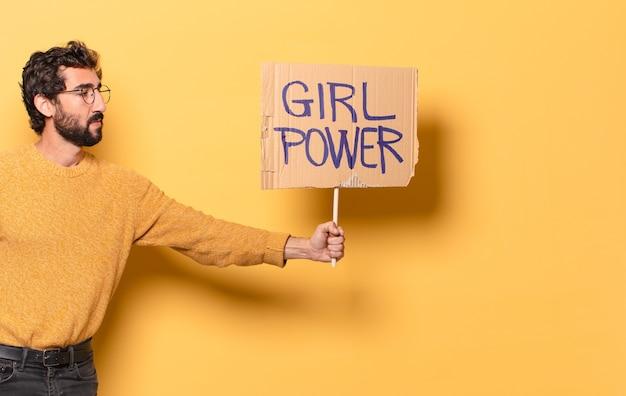Jonge gekke bebaarde man met een bordje van de macht van het meisje