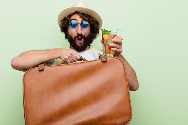 Jonge gekke bebaarde man met een cocktail. reis concept