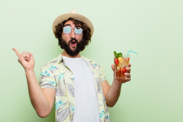 Jonge gekke bebaarde man met een cocktail. toeristisch concept