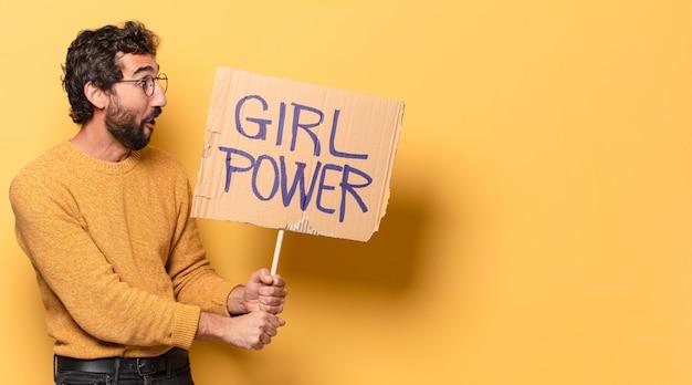 Jonge gekke bebaarde man met een girl power banner