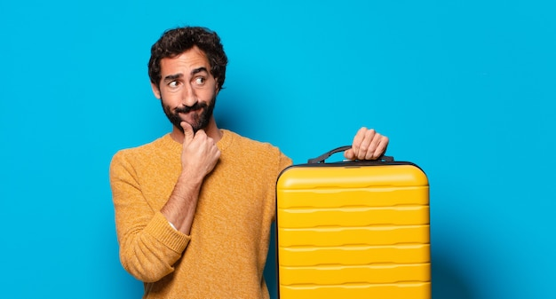 Jonge gekke bebaarde man met een koffer