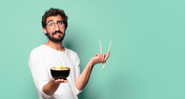 Jonge gekke bebaarde man met een noodle ramen bowl ramen