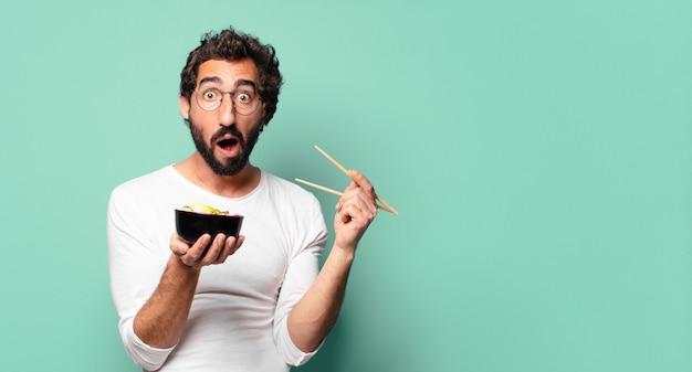 Jonge gekke bebaarde man met een noodle ramen bowl